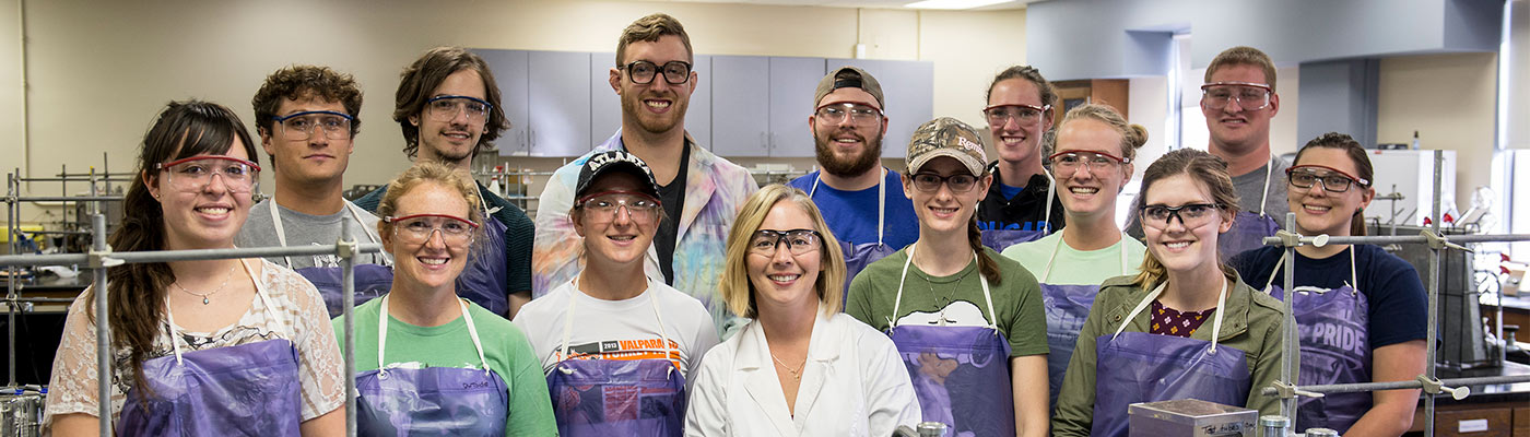 Group of biology students smiling with their professor.