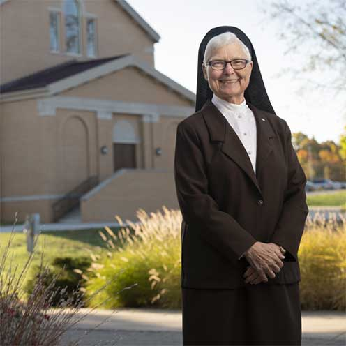 Sr Elise standing in front of the USF Chapel